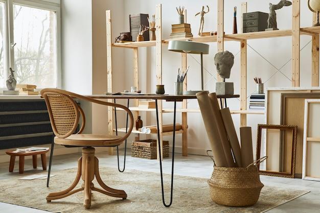 Espaço de trabalho de artista exclusivo com mesa elegante, cavalete de madeira, estante de livros, obras de arte, acessórios de pintura, decoração e objetos pessoais elegantes. sala de trabalho moderna para artista.