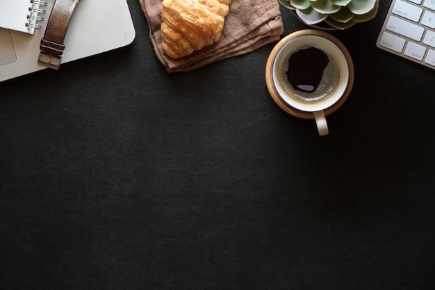Espaço de trabalho de couro escuro de mesa de escritório com preto café, material de escritório e espaço de cópia