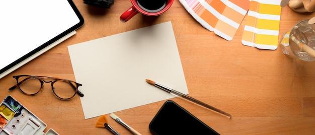 Espaço de trabalho de designer com ferramentas de papel, tablet e pintura de esboço de maquete