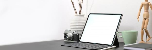 Espaço de trabalho de designer mínimo com tablet, câmera, suprimentos e decorações