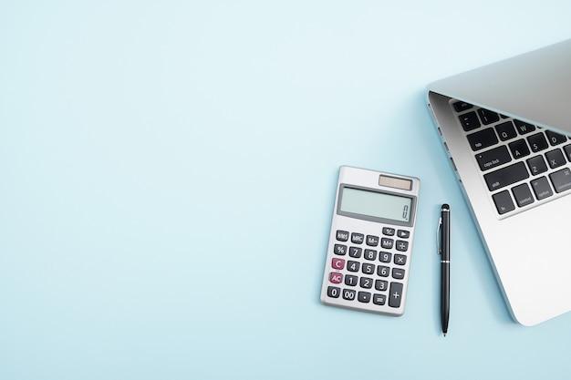 Espaço de trabalho de escritório com calculadora, caneta preta e laptop.