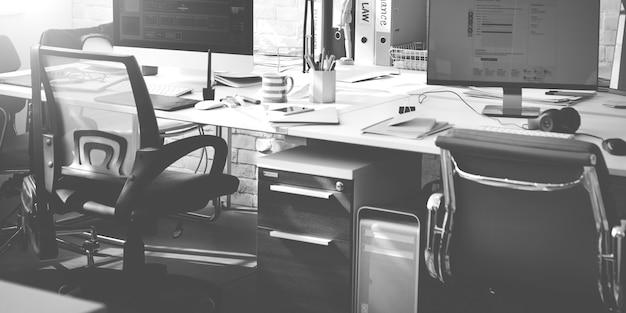 Espaço de trabalho de escritório com computadores em escala de cinza