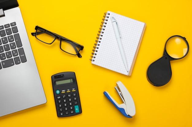 Espaço de trabalho de escritório com laptop, calculadora, óculos, grampeador e notebook.