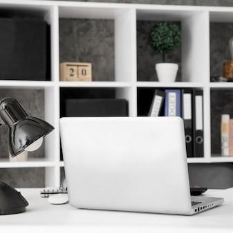 Espaço de trabalho de escritório com laptop e prateleira