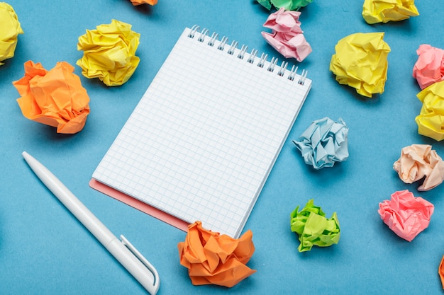 Espaço de trabalho de escritório com um caderno vazio, papel amassado
