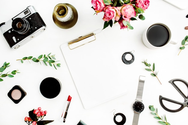 Espaço de trabalho de escritório doméstico feminino com área de transferência, laptop, flores rosas, ramos de eucalipto, acessórios de moda e cosméticos. camada plana, vista superior