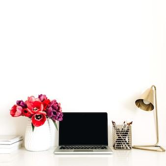 Espaço de trabalho de escritório em casa com laptop, buquê de flores de tulipa, artigos de papelaria, lâmpada