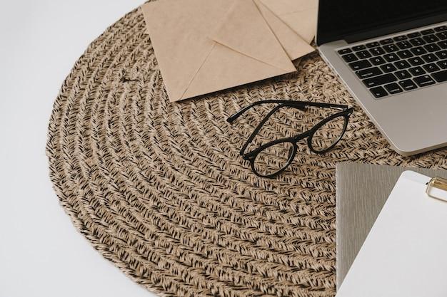 Espaço de trabalho de escritório em casa com laptop, óculos, bloco de transferência, envelopes