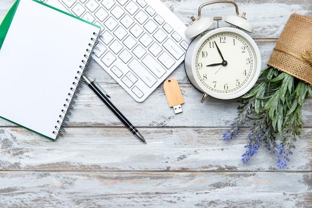 Espaço de trabalho de escritório em casa com teclado de computador e planta verde em fundo de madeira