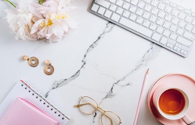 Espaço de trabalho de escritório em casa feminino com uma xícara de chá e flores de peônia na vista superior de fundo de mármore branco.