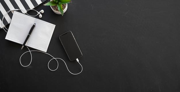 Espaço de trabalho de escritório em preto e branco com material de escritório e espaço de cópia em fundo preto