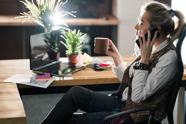 Espaço de trabalho de escritório moderno. estilo de negócios relaxado e conveniente. mulher fazendo pedidos ao telefone com uma xícara de café na mão.