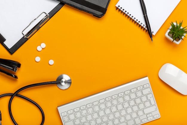 Espaço de trabalho de médico com equipamentos médicos na mesa amarela com vista superior