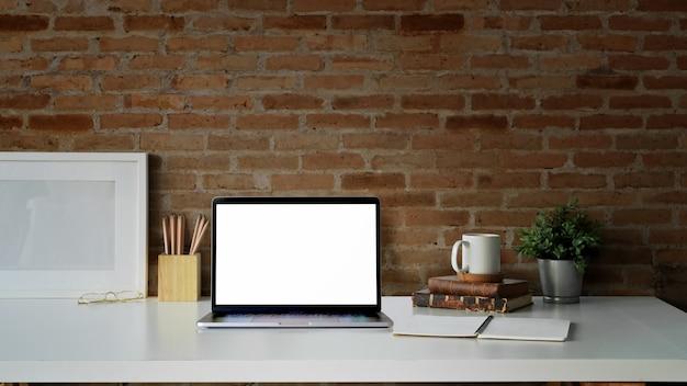 Espaço de trabalho de mesa criativa com porta-retrato em branco, laptop de tela em branco