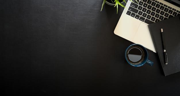 Espaço de trabalho de mesa de couro escuro de negócios com laptop e copyspace