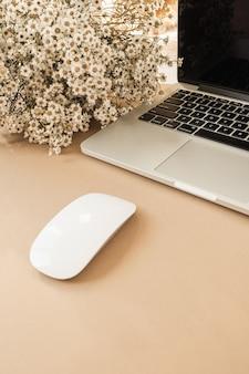 Espaço de trabalho de mesa de escritório em casa com laptop, buquê de flores de margarida de camomila em fundo bege pastel.
