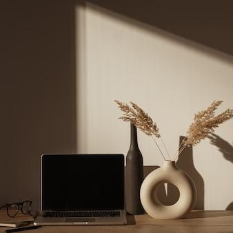 Espaço de trabalho de mesa de escritório em casa estético com sombras de luz solar na parede.