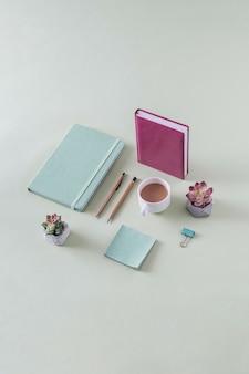 Espaço de trabalho de negócios bacana, natureza morta com espaço de cópia em verde com diário, diário, bloco de notas, flores, flores, clipe de papel e caneca de café em uma vista de alto ângulo