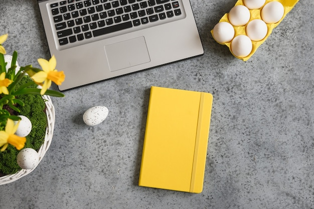 Espaço de trabalho de páscoa com flores amarelas de caderno e laptop para planejamento de férias e compras