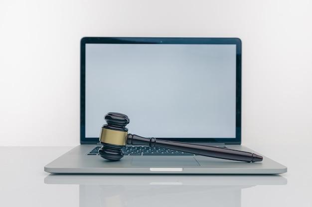 Espaço de trabalho do advogado com tela branca em branco do laptop e martelo de madeira legal, livro jurídico