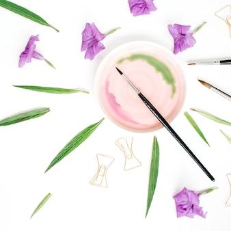 Espaço de trabalho do artista com aquarela, pincéis, clipes dourados, folhas verdes