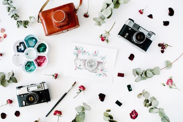 Espaço de trabalho do artista com câmera fotográfica retrô vintage e câmera pintada em aquarela, rosas vermelhas e arranjo de eucalipto