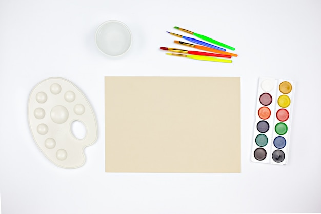 Espaço de trabalho do artista com paleta de aquarela, pincéis e papel