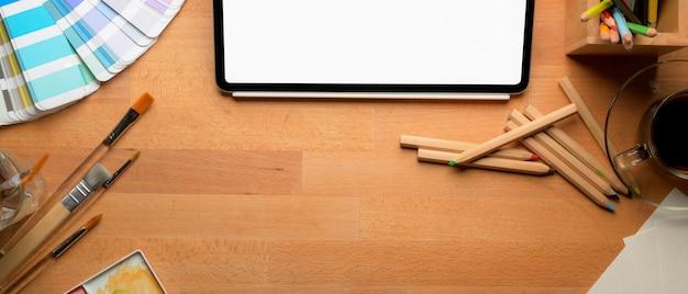 Espaço de trabalho do artista com tablet mock-up, ferramentas de pintura e espaço de cópia