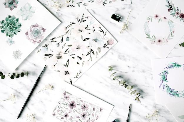 Espaço de trabalho do artista. pinturas em aquarela com molduras e flores
