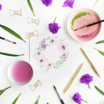 Espaço de trabalho do artista. quadro de guirlanda floral pintado com aquarela, pincéis, caneta e clipes dourados, folhas verdes