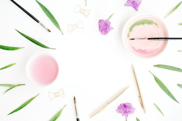 Espaço de trabalho do artista. quadro em aquarela, pincéis, caneta e clipes dourados, folhas verdes