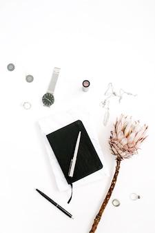 Espaço de trabalho do blogger ou freelancer com flor protea, caderno e acessórios femininos em fundo branco. mesa plana, vista de cima com decoração minimalista e decoração minimalista. conceito de blog de beleza.