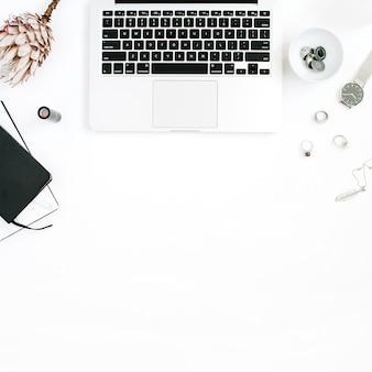 Espaço de trabalho do blogger ou freelancer com laptop, flor protea, caderno e acessórios femininos em fundo branco. mesa plana, vista de cima com decoração minimalista e decoração minimalista. conceito de blog de beleza.