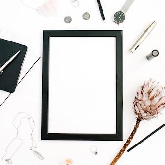 Espaço de trabalho do blogger ou freelancer com moldura de foto em tela em branco, relógios protea, caderno de flores e acessórios femininos em fundo branco vista plana de cima mesa de escritório em casa
