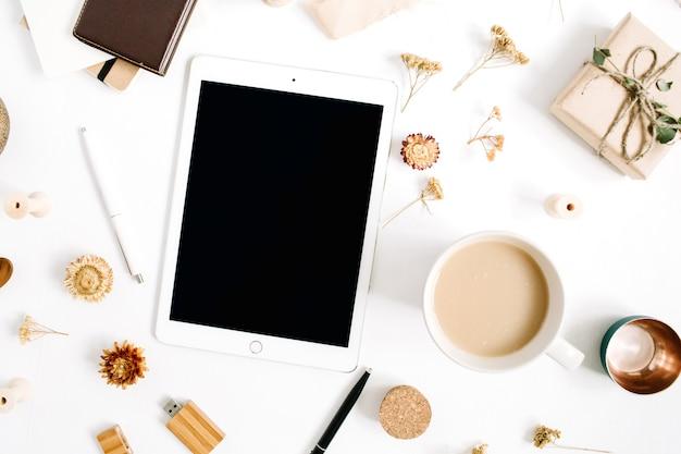 Espaço de trabalho do blogger ou freelancer com tablet, caneca de café, caderno e acessórios em fundo branco. mesa de escritório em casa de estilo minimalista em marrom horizontal, vista superior. conceito de blog de beleza.