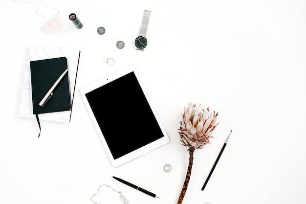 Espaço de trabalho do blogger ou freelancer com tablet de tela em branco, flor protea, caderno, relógios e acessórios femininos em fundo branco. mesa plana, vista de cima com decoração minimalista e decoração minimalista.