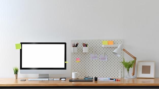 Espaço de trabalho do designer criativo com o computador vazio de exibição.
