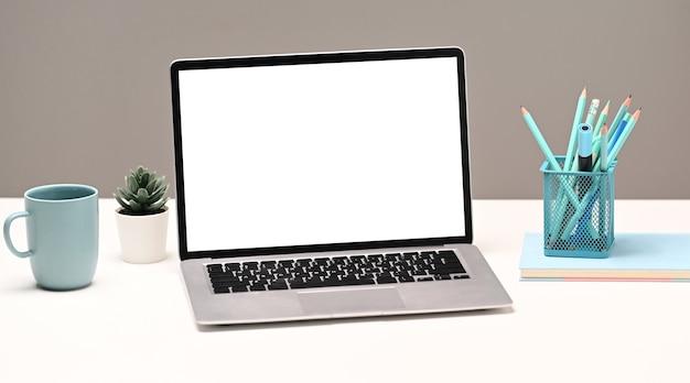 Espaço de trabalho do designer criativo com simulação de computador portátil, caderno, artigos de papelaria e xícara de café.