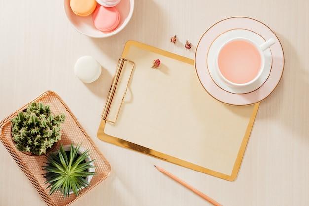 Espaço de trabalho do escritório doméstico feminino com área de transferência, biscoitos, caneta, caneca de café em fundo pastel. conceito de estilo de vida de vista superior plana leigos.