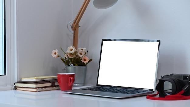 Espaço de trabalho do fotógrafo ou designer com laptop de tela em branco branca e equipamentos na mesa branca.