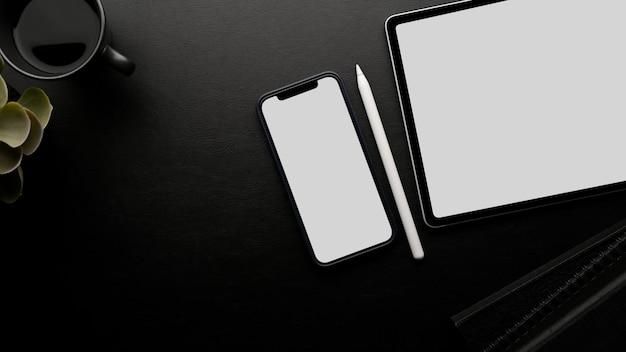 Espaço de trabalho do smartphone e da maquete da tela do tablet, caneta stylus, espaço de cópia e decoração em fundo preto