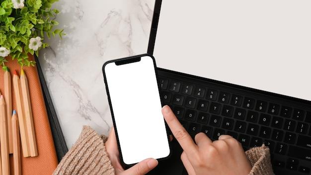 Espaço de trabalho elegante com mãos femininas usando maquete de smartphone e maquete de fundo de mármore