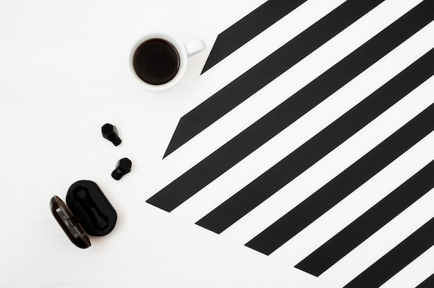 Espaço de trabalho elegante e minimalista com xícara de café, fones de ouvido sem fio