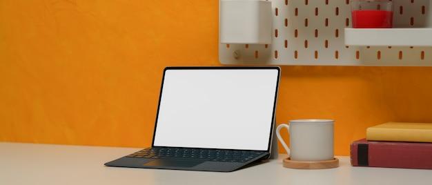 Espaço de trabalho elegante tablet com copo, cópia espaço, livros e prateleira na parede amarela
