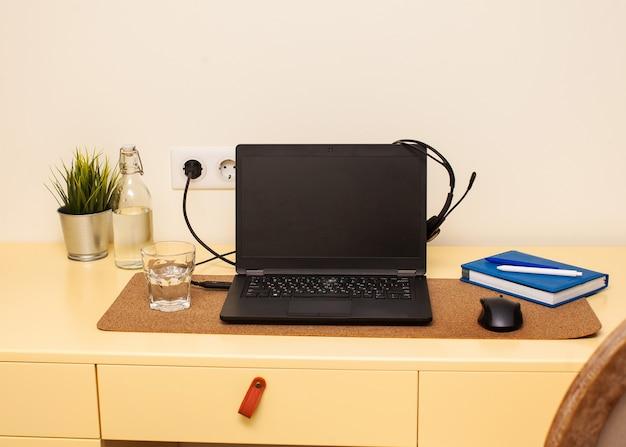 Espaço de trabalho em casa, laptop, fones de ouvido, caderno de trabalho