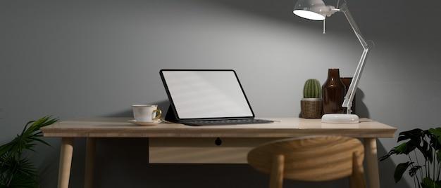 Espaço de trabalho em casa tarde da noite trabalho com luz baixa laptop de escritório em tela vazia na mesa de madeira