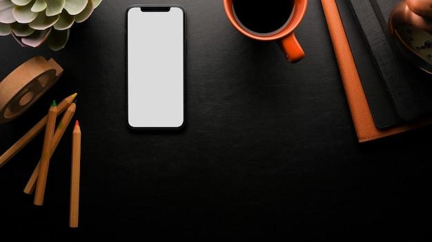 Espaço de trabalho em fundo preto com cópia espaço do smartphone maquete lápis de cor café preto