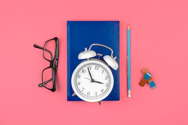 Espaço de trabalho escolar rosa com despertador, diário de caderno e despertador no fundo da mesa, foto da vista superior