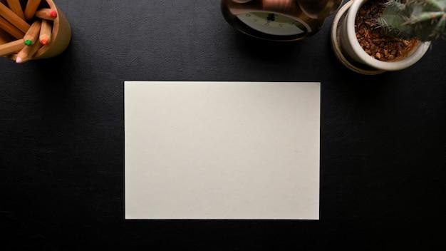 Espaço de trabalho escuro com folha de papel em branco para a vista superior do plano de fundo da mesa em preto de texto