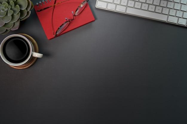 Espaço de trabalho escuro da tabela da mesa do escritório com computador, materiais de escritório e caneca de café.